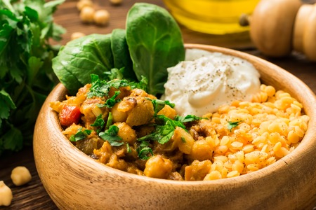 Pumpkin, red lentil and chickpea curry in wooden bowl