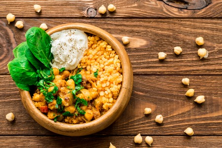 Ready to eat creamy vegan chickpea curry and greek yogurt in wooden bowl