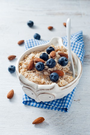 A dietary healthy oatmeal dish with almond and blueberry