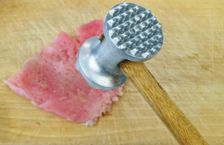 Tenderize slabs of meat on wooden board photo