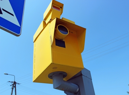 A traffic speed monitoring camera, against a bright blue sky