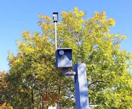 Traffic speed monitoring camera, against a bright blue sky  photo
