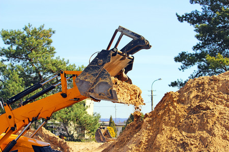 earth moving: Wheel loader Excavator unloading sand with water during earth moving works at construction site
