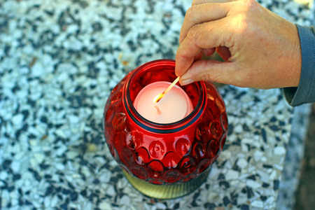 Woman at cemetery is lighting a red candle