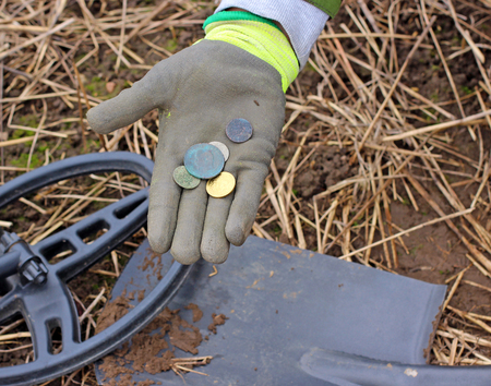 metal detector: Searching with a metal detector. Coins in hand. Stock Photo