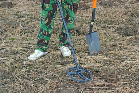 golden shovel: Searching with metal detector .Old medieval gold coin in hand. Stock Photo