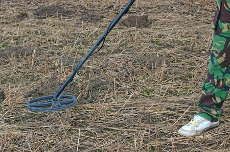 gold shovel: Searching with metal detector .Old medieval gold coin in hand. Stock Photo