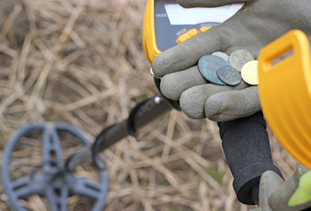 detecting: Searching with a metal detector. Coins in hand. Stock Photo