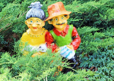 Two gnomes in conifers in the garden
