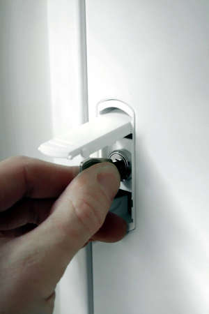 fuse box: Hand unloking the fuse box  with a key. Stock Photo