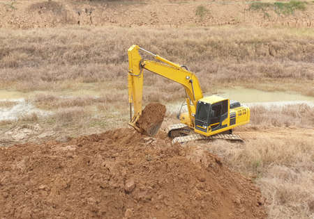 A yellow backhoe is digging a big pond.
