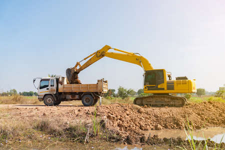 Backhoe loader soil from the ground up to dump truck. Archivio Fotografico