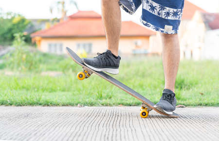 Young man doing a skateboard trick on a road in front of home. Skateboarders Feet Close Up.