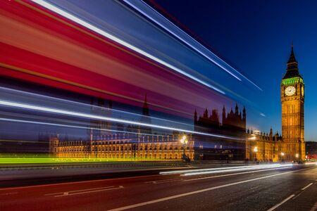 Big Ben w Londynie nocą z typowym londyńskim czerwonym autobusem o nazwie