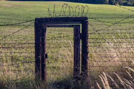 Remains of iron curtain and memorial of  regime - Cizov, Czech republic - door in fence at the border 版權商用圖片
