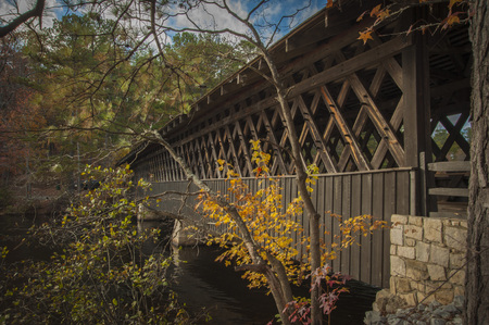 Wooden Bridge over Tennesseee extending over a river and surrounded by trees with leaves showing autumn colors.  Commercial use