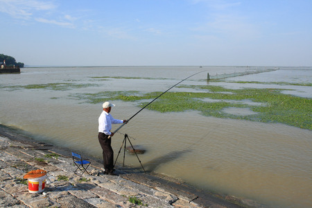guyan: An old man fishing at the lakeside Stock Photo