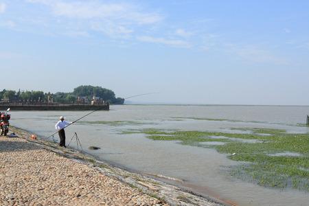 guyan: An old man fishing at the lakeside Editorial