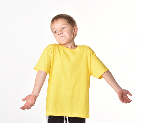 Child in a T-shirt. Emotional portrait of a teenage boy. The boy is surprised. The boy has no answer.