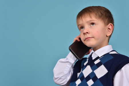A teenager communicates on a mobile phone. The boy has a telephone. Business conversation.