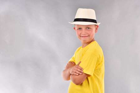 The boy in the hat. A young man in a yellow T-shirt.