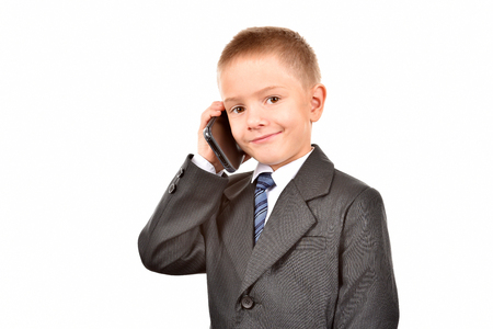 The boy is talking on the phone. A child in a suit.