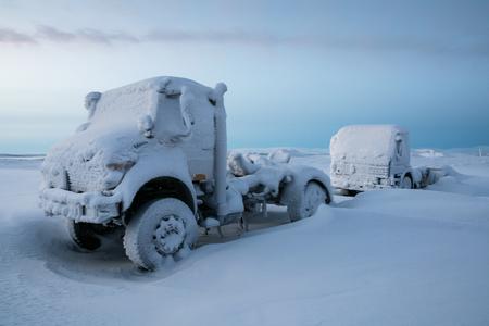 Two frozen truck parking in the deep snow beyond the polar circle, Kiruna, Sweden Stock Photo