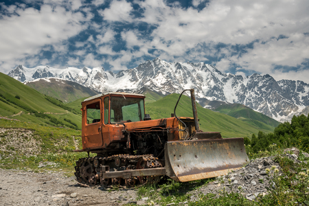 Old rusty corroded belt bulldozer parking in mountain landscape under the highest Georgian mountain Shkhara. Caucasus, Svaneti region, Georgia Imagens