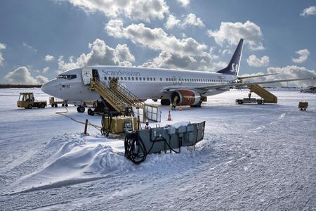 SWEDEN, KIRUNA AIRPORT - FEBRUARY 26, 2012: SAS Scandinavian airlines airplane during last control procedures before departure. Snow condition.