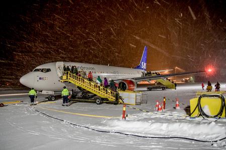SWEDEN, KIRUNA AIRPORT - JANUARY 12, 2012: SAS Scandinavian airlines airplane shortly before departure. Snow storm.
