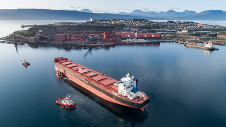 Aerial shot of a cargo ship approaching port terminal with help of towing ship, Narvik, Norway 写真素材