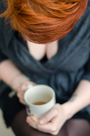 casey: Young girl holding a cup of tea. Top view.