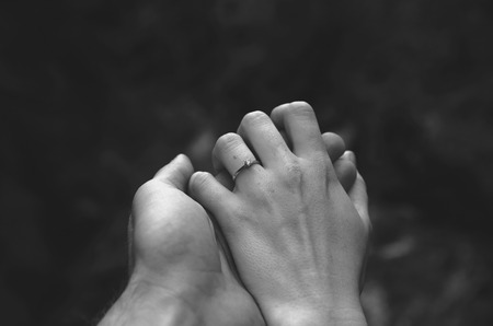 trust people: Hands of a young couple holding each other. Girl is wearing an engagement ring.