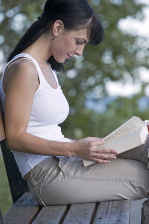 beautiful brunette sitting down reading book Stock Photo - 515495