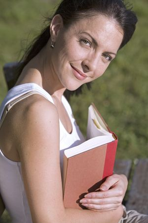beautiful brunette sitting down reading book