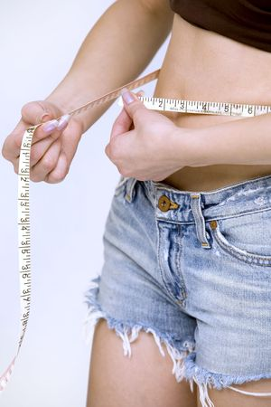 woman measuring her waist wearing jeans shorts Stock Photo