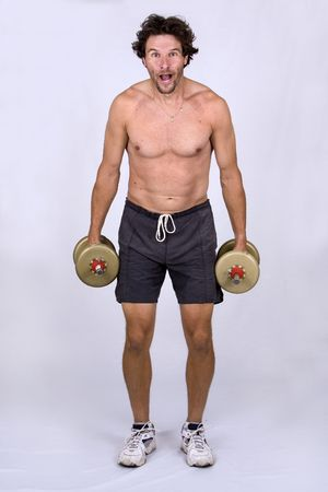 athletic man holding weights while making faces