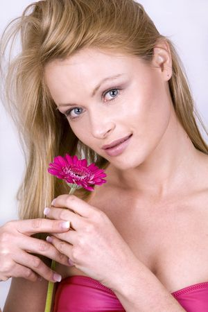 beautiful blond woman holding bright flower on isolated white background photo