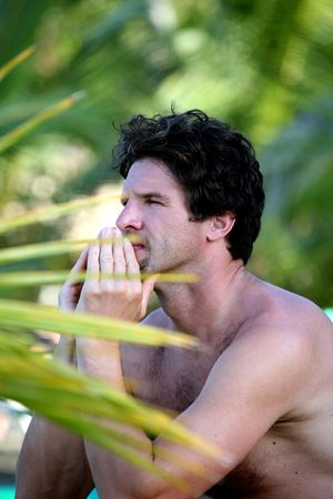 attractive man sitting on the beach under palm trees Stock Photo