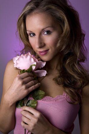stunning blond model holding pink rose wearing pink tank top photo