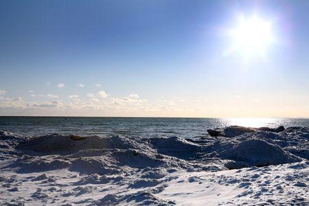 beautiful winter nature scene, snow and ice around ocean, sun photo