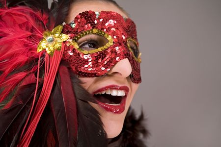 mysterious brunette wearing carnival red mask on her face photo