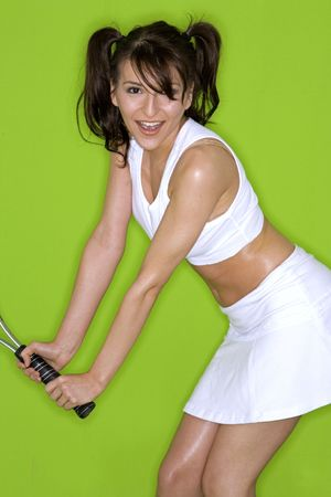 active young brunette wearing white outfit playing tennis photo
