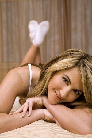 Sous-vêtements blancs de port de belle femme et pose dans son lit Banque d'images - 785611
