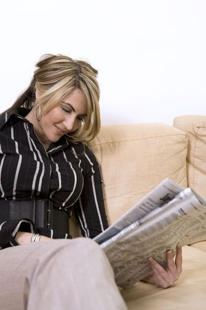 beautiful woman sitting on the sofa in living room wearing businesss wear and reading newspaper