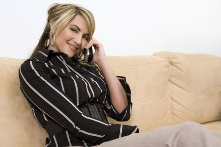 beautiful woman sitting on the sofa in living room wearing businesss wear and talking on the phone Banco de Imagens