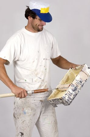 young man working as painter, on isolated background wearing white outfit