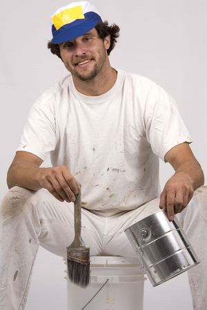 house painter: young man working as painter, on isolated background wearing white outfit