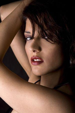 Bella bruna indossando bikini nero su sfondo nero isolato