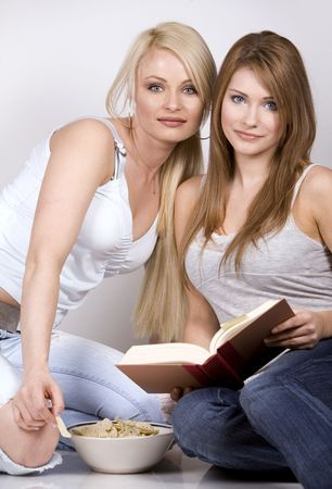two pretty womem on grey background eating chips and reading book Stock Photo - 960530